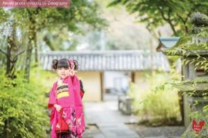 三歲小女孩穿著七五三和服舉起三隻手指拍攝家庭記念照